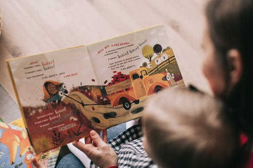 woman reading book to toddler - 6 Ways to Make Sure that You Offer Great Customer Support at Your Preschool