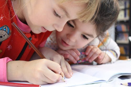 girls on desk looking at notebook USA Keep it easy and focused - The 2 Main Steps of Using a Survey to Start Your Preschool